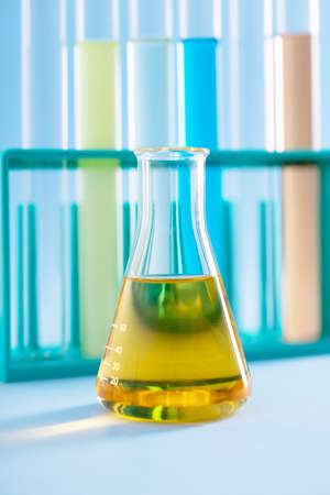 A vertical closeup shot of an Erlenmeyer flask with yellow liquid and test tubes in the background at a lab