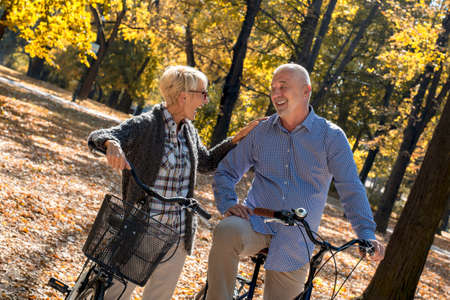 An elderly couple standing with their bikes and smiling in a park