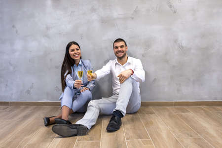 A young couple drinking wine while sitting on the floor celebrating moving into new apartment