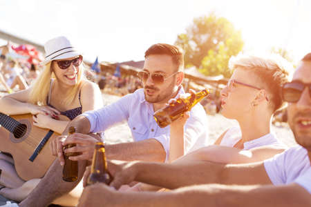 A shallow focus shot of young happy Caucasian friends drinking beer in the beach with a guitar
