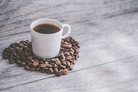 A closeup shot of a cup of coffee on heart-shaped coffee beans on a wooden surface
