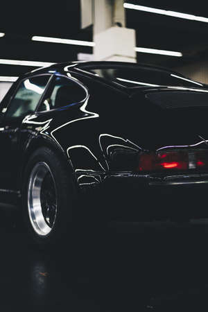 A vertical shot of a parked black car with a blurry background