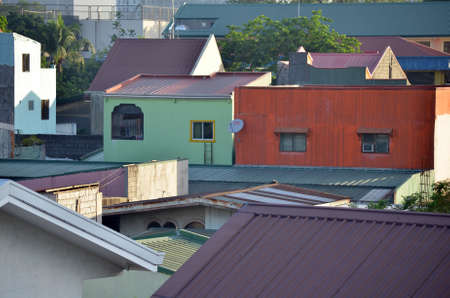 A wide shot of colorful houses with brown rooftops