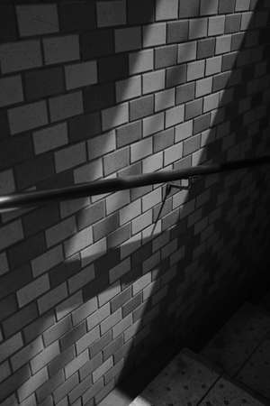 A vertical grayscale shot of a handrail on a brick wall