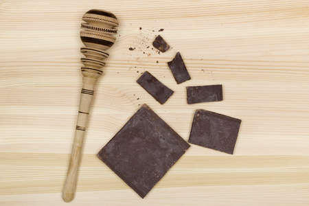 A high angle shot of pieces of chocolate and a chocolate beater on a wooden surface