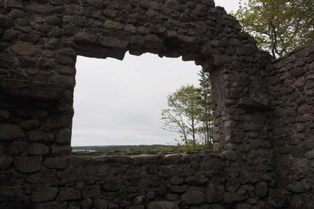 The ruins of an old and forgotten lodge in a field captured during the daytime