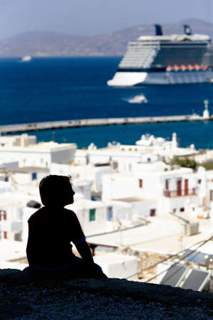 Young boy looking at the horizon a cruise ship, in a sunny day. At his feet the white town of Cora, the main center of Mykonos island Banco de Imagens