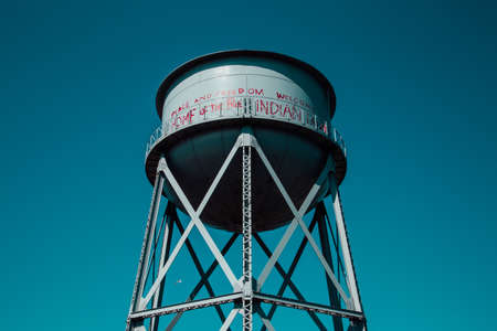 A low angle shot of a water tower with peaceful writings on it on a blue beautiful background