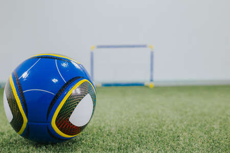 A selective focus shot of a blue soccer ball in a children's playground