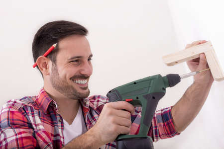 A smiling Caucasian male mounting wood shelf with a drill and repairing home