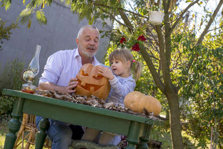 A happy family carving pumpkin together and enjoying a day together
