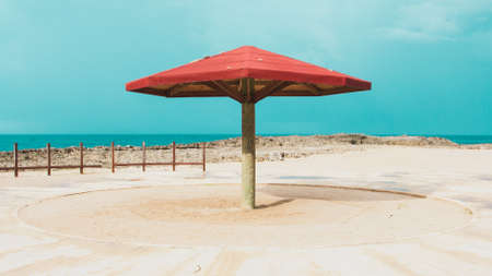 A wide shot of a wooden large red parasol at the beach under a blue beautiful sky on a sunny day