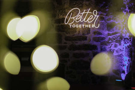 """A neon light text """"Better together"""" on a stone wall with bokeh lights effect"""