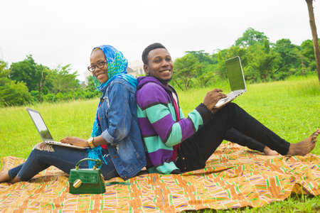 A Nigerian couple working on their laptops while on a picnic on the grass-covered meadow
