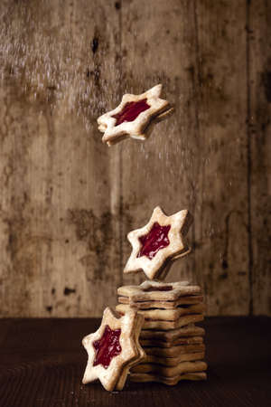 A vertical shot of a tower of star-shaped jam cookies on a wooden surface with a wooden background