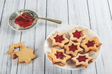 A high angle shot of star-shaped cookies filled with jam on a plate on a wooden white surface 写真素材