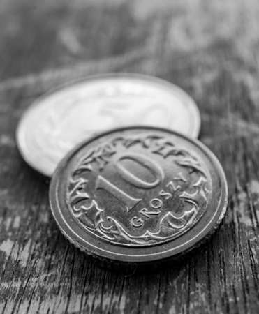 POZNAN, POLAND - Jul 03, 2020: Close up of a small Polish ten groszy coin on a wooden surface in soft focus background and monochrome tones