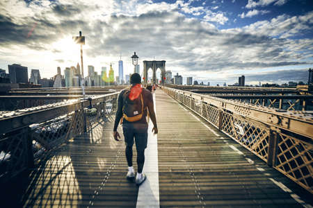 A male walking on a bridge coming back from Brooklyn to Manhattan with New York skyline in the background