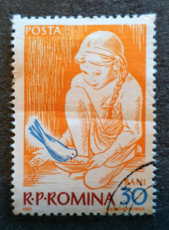 SOVATA, ROMANIA - Jul 02, 2020: an old stamp from Romania, 1962 edition with the image of a little girl feeding a pigeon