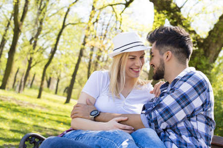 An attractive young couple flirting and having fun on a park bench