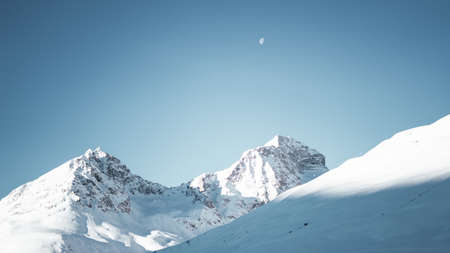 A wide shot of mountains covered in snow under a clear blue sky with a half moon