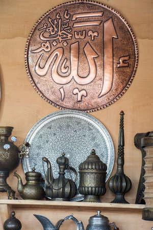 """A vertical image of decorative brass jars and plates with the word """"Allah"""" in Arabic calligraphy"""