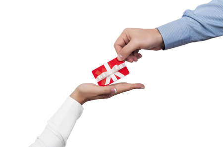 A closeup shot of a male hand giving a gift card to a female hand on a white background