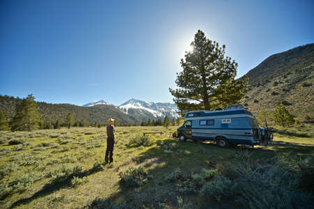 A beautiful shot of a female standing on a grassy field near a van with mountain and a clear sky in the background