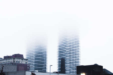 A wide shot of gray architectural high rise building covered in fogs