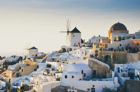 A wide shot of white cliff houses and windmills in Thira, Santorini, Greece