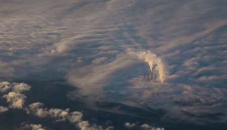 An aerial shot of a power station smoke high above in a sky covered with clouds