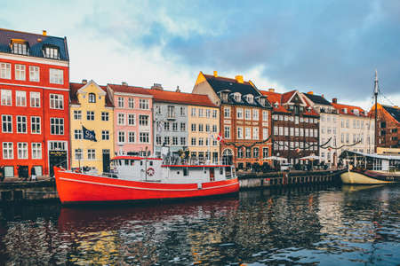 A wide shot of a red and white boat on the body of water near a port with colorful houses in Nyhavn, Denmark