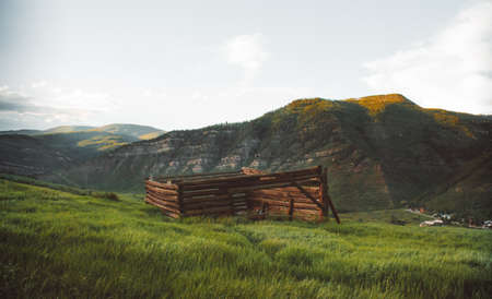 A beautiful shot of a broken wooden house in a grassy field with mountains in the background 写真素材