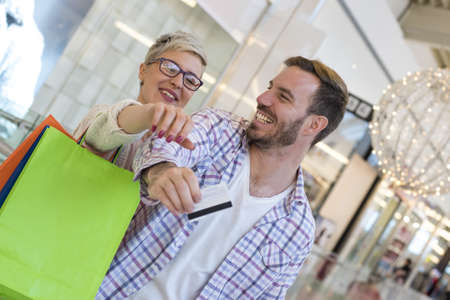 A shallow focus shot of a happy Caucasian couple doing shopping in the shopping centre