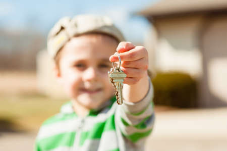 A selective focus shot of a keychain on a blurred young boy's finger