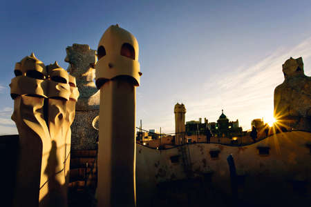 A closeup of the famous sculpture of the Casa Mila chimneys with a sun glare in the background