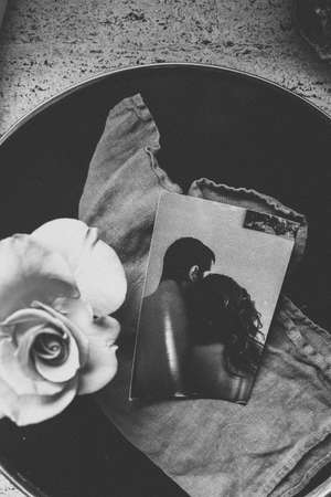 A vertical greyscale shot of a photograph of two lovers next to a flower in a bucket