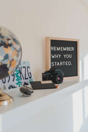 "A shallow focus shot of black SLR camera on a white wooden shelf with a quote ""Remember why you started"" on a board next to it"