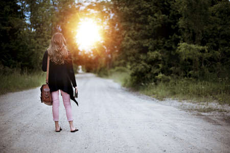 A selective shot of a female with brown bag standing in the middle of a path surrounded by trees during sunrise