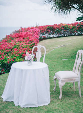 A small round table with two white chairs in a garden with beautiful red roses on a sunny day