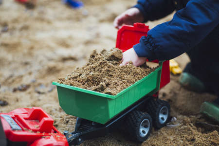 A closeup shot of a toddler playing with sand and construction toys in the park during daytime Standard-Bild