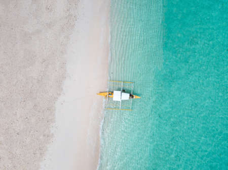 An aerial shot of a sandy beach and crystal clear water with a boats in it