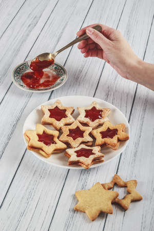 A vertical high angle shot of person decorating star-shaped cookies with jam on a wooden white surface