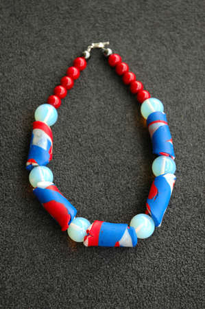 A vertical shot of a necklace made of blue and red beads on a gray surface