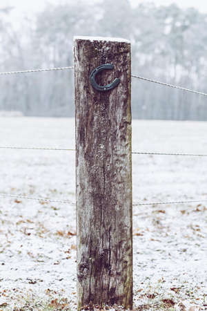 A vertical shot of a horseshoe nailed to a wooden fence with a blurred background