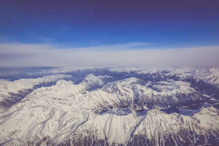 An aerial shot of snowy mountains under a clear blue sky