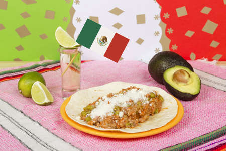 A closeup shot of a traditional mexican dish next to a shot of tequila and a sliced avocado Stock Photo