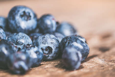 A closeup of ripe fresh blueberries on a brown wooden surface