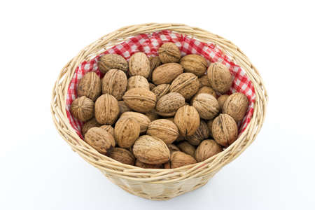A close up shot of Greek walnuts in a basket isolated on a white background