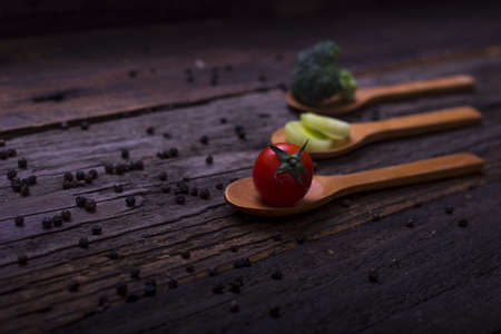 A closeup shot of wooden spoons with small vegetables on them placed in a wooden table Reklamní fotografie